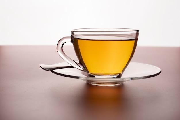 Une tasse de thé chaud fraîchement infusé dans un verre sur la table.