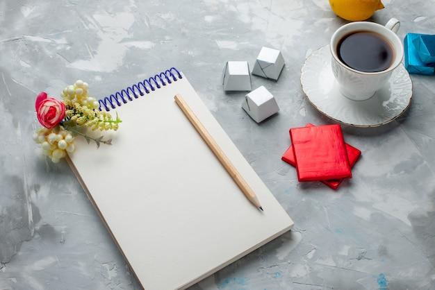 Tasse de thé chaud à l'intérieur tasse blanche avec bloc-notes de bonbons au chocolat et paquet d'argent sur un bureau léger, boire des biscuits sucrés à l'heure du thé