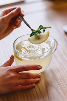 Une tasse de thé chaud à la menthe et au citron mélange la fille avec une cuillère