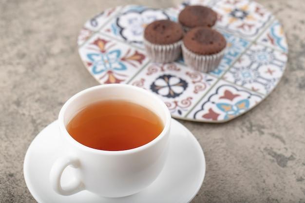 Tasse de thé chaud avec des mini gâteaux au chocolat sur table en pierre.