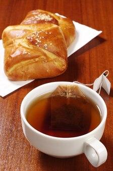 Tasse de thé chaud avec sachet de thé et petits pains sucrés sur table
