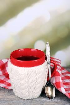 Tasse de thé chaud savoureux, sur table en bois, sur fond clair