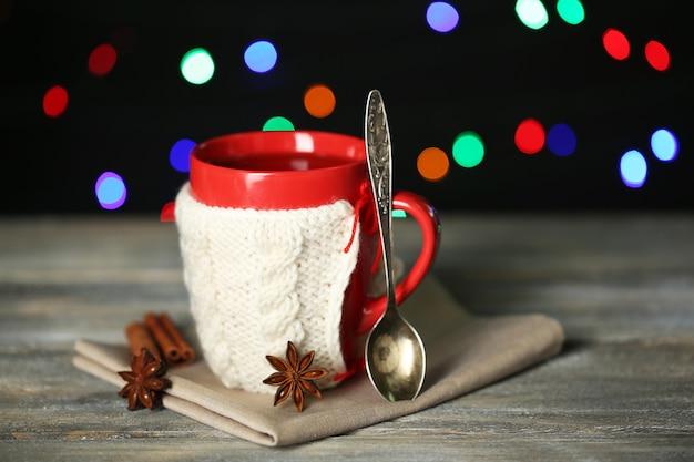 Tasse de thé chaud savoureux, sur table en bois, sur surface brillante