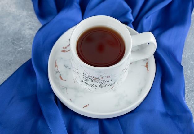 Tasse de thé chaud sur tissu bleu.