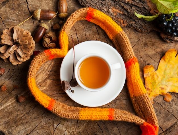 Tasse à thé chaude avec une écharpe sur fond en bois