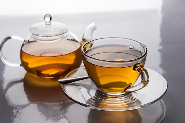 La tasse à thé chaude et la théière transparente sur la table avec espace copie.