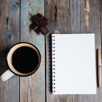 Tasse de thé, chocolat et stylo, cahier sur une table en bois, flatlay