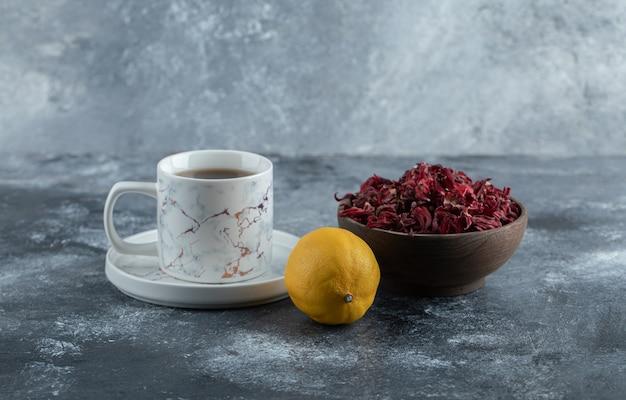 Tasse de thé, citron et bol de fleurs séchées sur table en marbre.