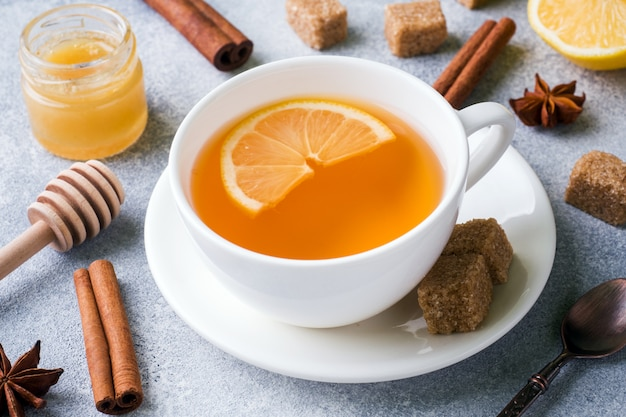 Tasse de thé avec citron et cassonade, cannelle et anis sur la table.