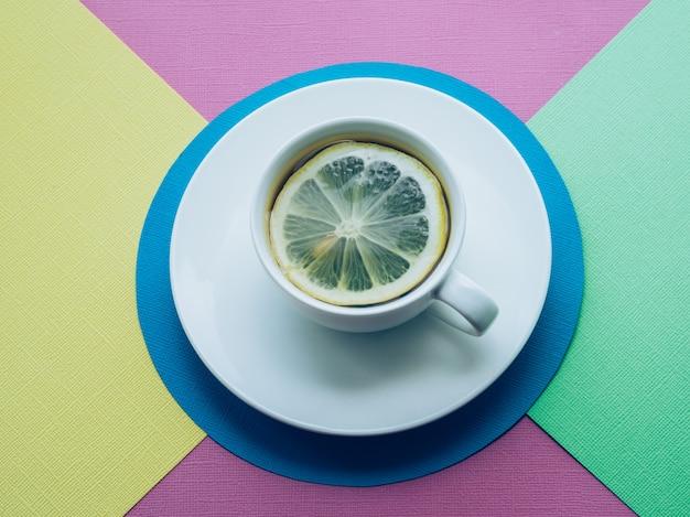 Tasse de thé et de citron fond de papier coloré.