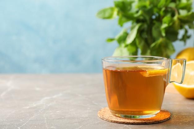 Tasse de thé, citron et menthe sur fond gris, espace pour le texte