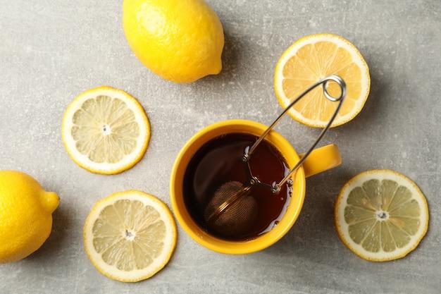 Tasse de thé et citrons sur fond gris, vue de dessus