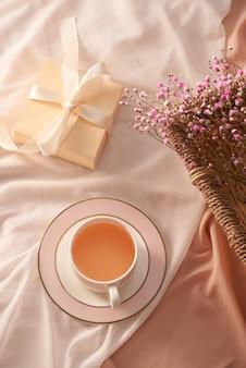 Tasse de thé, coffret cadeau et fleurs sur fond clair