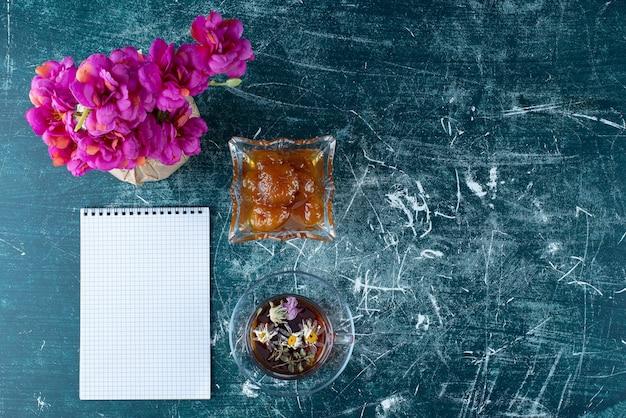 Une tasse de thé avec confiture de figues dans la soucoupe.