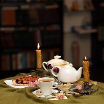 Tasse de thé contre une bougie, un gâteau, des fleurs et des photographies anciennes