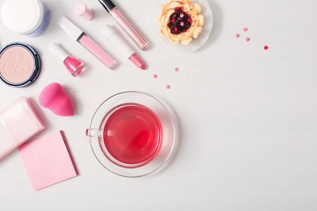 Tasse de thé avec des cosmétiques féminins sur table en bois blanc