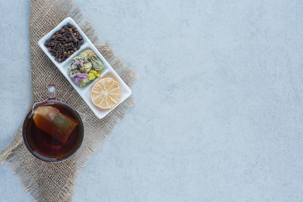 Une tasse de thé à côté d'un bol de feuilles de lemonnd tranchées sèches sur une serviette sur du marbre.