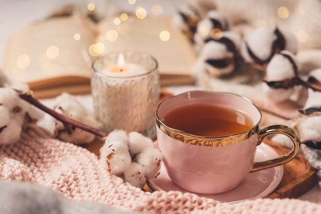 Tasse de thé, coton, douillet, livre, bougie. concept automne hiver confortable.