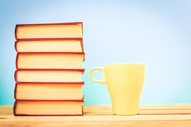 Tasse de thé de couleur avec des livres sur la table