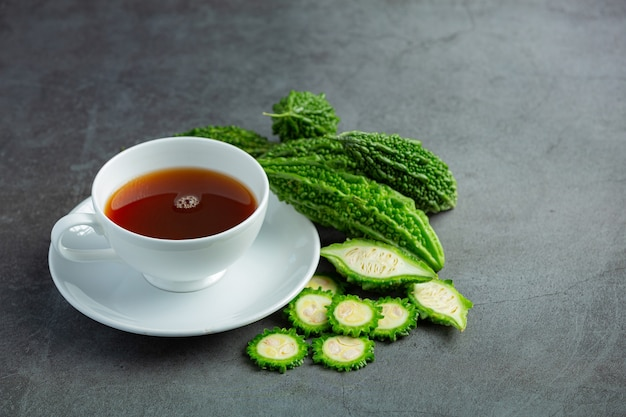 Une tasse de thé de courge amère chaud avec des tranches de gourde amère crue sur un sol sombre