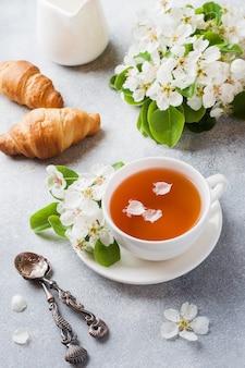 Tasse de thé et croissant sur gris