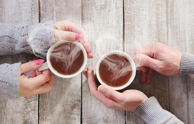 Une tasse de thé dans les mains d'un homme et d'une femme. mise au point sélective.