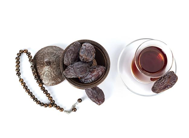 Une tasse de thé avec des dates sur une assiette isolée