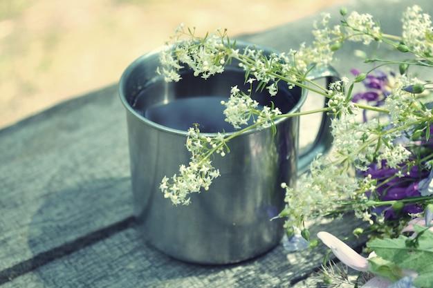 Tasse de thé debout sur une table avec des fleurs épanouies, filtre