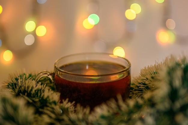 Une tasse de thé décorée de guirlandes du nouvel an sur fond de guirlandes étincelantes.