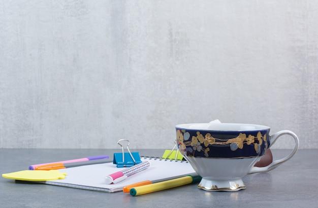 Une tasse de thé délicieux avec des crayons et une feuille de papier.