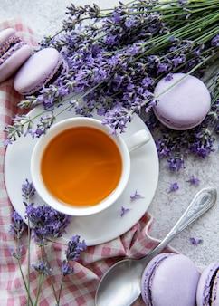 Tasse de thé avec dessert macaron à la lavande et fleurs de lavande fraîche