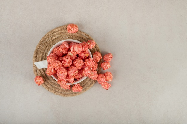 Tasse de thé sur un dessous de plat débordant de pop-corn rouge sur marbre.