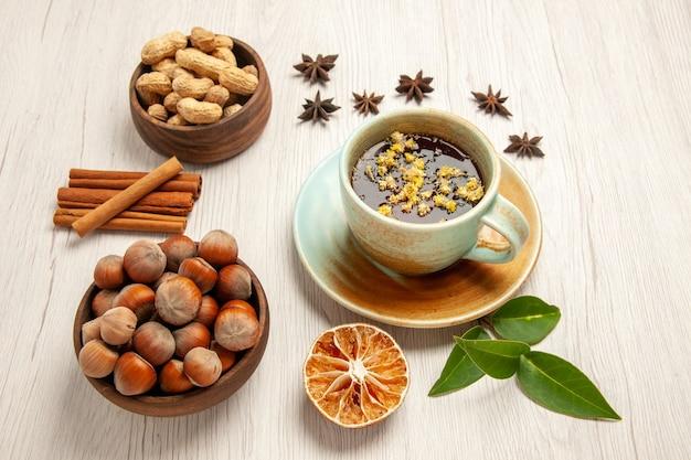 Tasse de thé avec différentes noix sur blanc