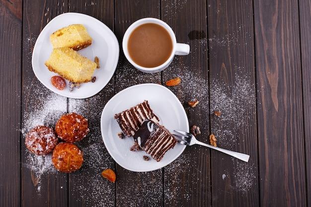 Tasse de thé avec du lait et deux assiettes avec un gâteau au fromage et un gâteau au chocolat