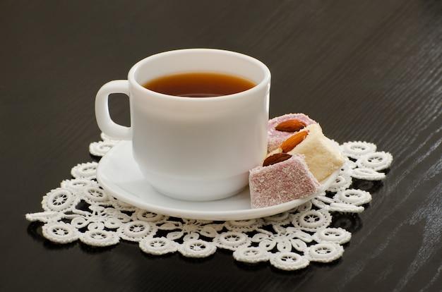 Tasse de thé du matin, délice turc dans une soucoupe sur le bureau noir