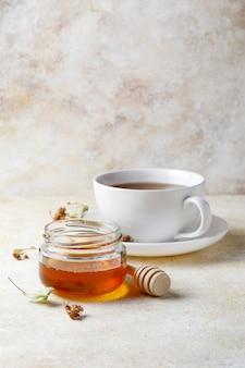 Tasse de thé avec du miel et une théière