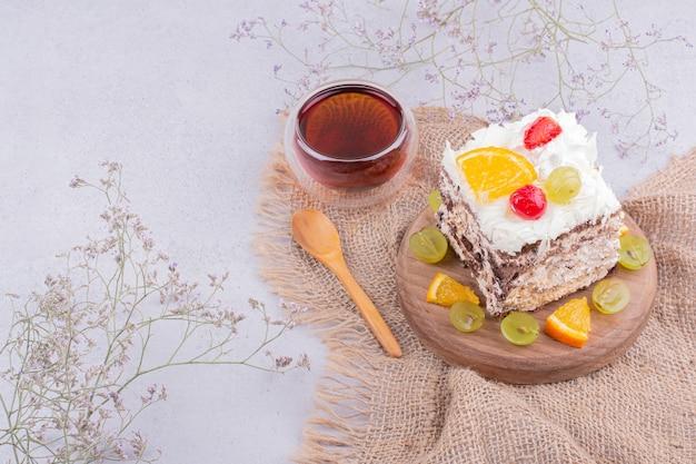 Une tasse de thé earl grey avec une tranche de gâteau aux fruits