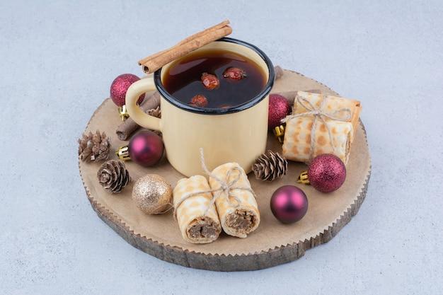 Tasse de thé à l'églantier, biscuits et boules sur planche de bois.