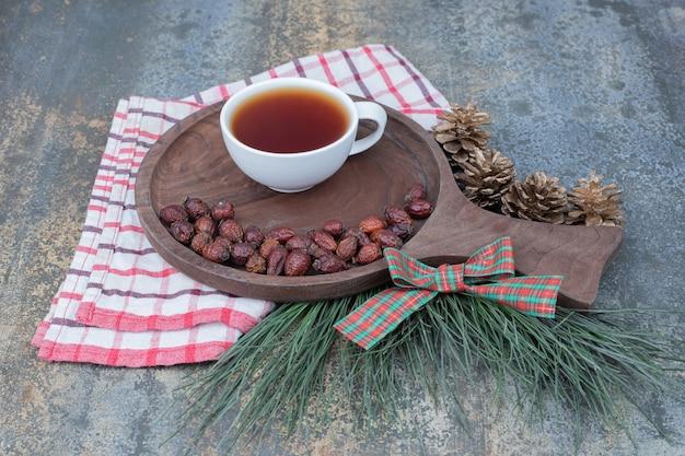 Tasse de thé et d'églantier séché sur planche de bois. photo de haute qualité