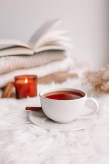 Une tasse de thé sur la fenêtre avec des bougies allumées et des pulls.