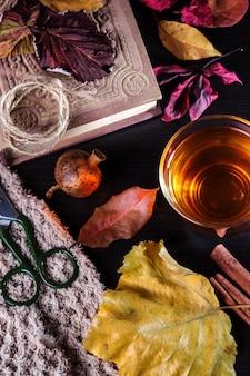 Une tasse de thé avec des feuilles d'automne et un livre