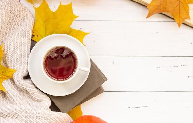 Une tasse de thé, des feuilles d'érable jaunes, des livres et une chose tricotée, copyspace