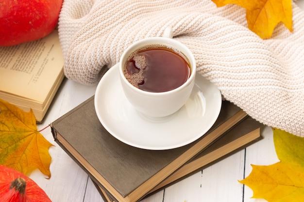 Une tasse de thé, des feuilles d'érable jaunes, des livres et un truc en tricot