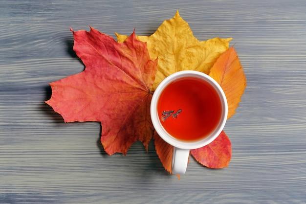 Tasse de thé sur les feuilles séchées d'automne et fond en bois.