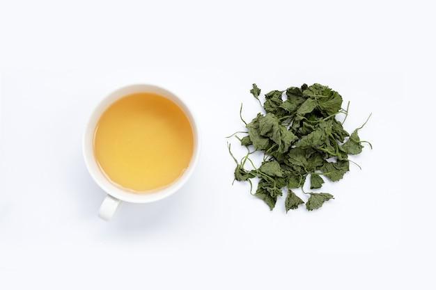 Tasse de thé avec des feuilles séchées de gotu kola sur fond blanc.