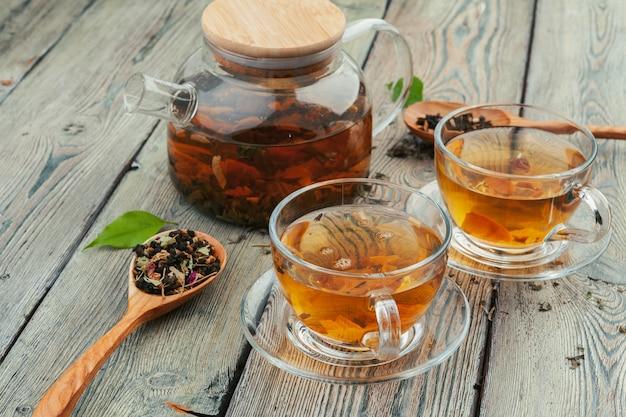 Tasse de thé et feuilles de thé sur table en bois