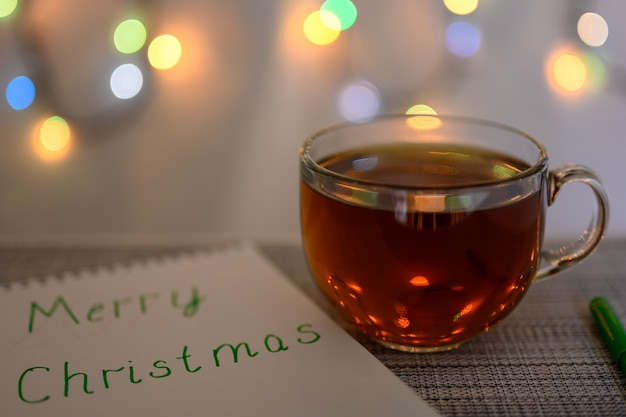 Une tasse de thé, un feutre et un cahier avec l'inscription joyeux noël sur fond de guirlandes scintillantes.