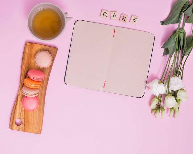 Tasse de thé de fines herbes; blocs de gâteau de texte; macarons; journal vierge et eustoma blanc sur fond rose