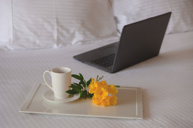 Tasse de thé avec une fleur jaune sur un lit blanc à côté d'un ordinateur portable. lieu de travail indépendant en voyage