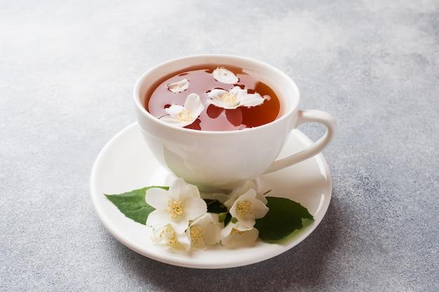 Tasse de thé avec des fleurs de jasmin sur une table grise
